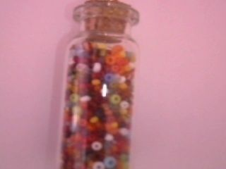 A cute tiny jar with small beads. .  Free tutorial with pictures on how to make a charm necklace in under 20 minutes using scissors, beads, and glue. Inspired by clothes & accessories. How To posted by Yaelle Q. Difficulty: Easy. Cost: Cheap. Steps: 4