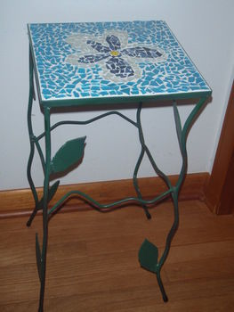 Floral table .  Make a table by creating, spraypainting, glassworking, metalworking, molding, soldering, and mosaic with spray paint, grout , and scrap. Inspired by flowers and floral. Creation posted by DJ Jenks. Difficulty: 5/5. Cost: 4/5.