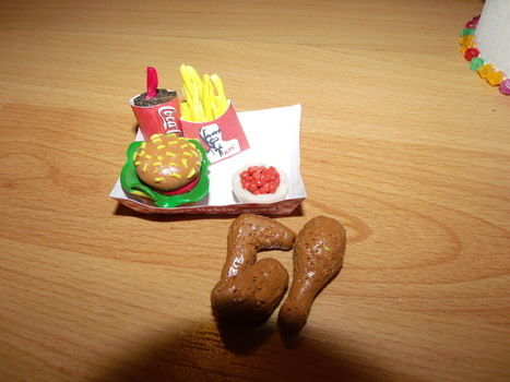 Finger lickin good!! .  Sculpt a clay burger in under 60 minutes by baking and molding with polymer clay, card, and fimo glaze. Inspired by chicken. Creation posted by Krafty Kitty Kat >'.'<.  in the Decorating section Difficulty: Easy. Cost: Cheap.