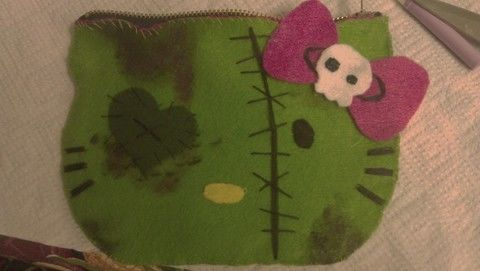 A cute zombie hello kitty pouch .  Make a food plushie by sewing and felting with fabric, felt, and buttons. Inspired by hello kitty, domo kun, and domo kun. Creation posted by kawaiicrafter. Difficulty: Simple. Cost: Cheap.