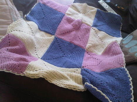 A quick, elegant baby blanket .  Stitch a knit patchwork blanket in under 120 minutes by needleworking, sewing, and crocheting with yarn. Inspired by babies, baby showers, and vintage & retro. Creation posted by RoJo. Difficulty: Easy. Cost: Absolutley free.