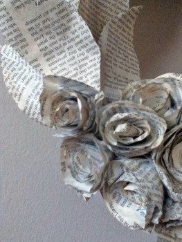 Roses and leaves made out of book pages and into a wreath. .  Make a paper wreath in under 180 minutes by dyeing, papercrafting, and paper folding with ribbon, hot glue, and foam. Inspired by roses. Creation posted by joceyfraz. Difficulty: 4/5. Cost: Cheap.