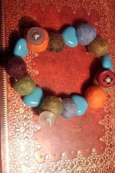 Felt beads and buttons bracelet .  Make a bracelet in under 10 minutes by creating, beading, and needleworking with beads, buttons, and stretchy string. Inspired by vintage & retro and clothes & accessories. Creation posted by AnaEma. Difficulty: Easy. Cost: Cheap.