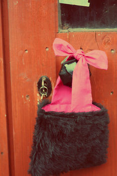 Small black fake fur 'tote' bag with pink bow handle detail. .  Sew a bow bag in under 120 minutes by sewing with needle, material, and interfacing. Inspired by clothes & accessories and bows. Creation posted by Lindeh. Difficulty: 3/5. Cost: Cheap.