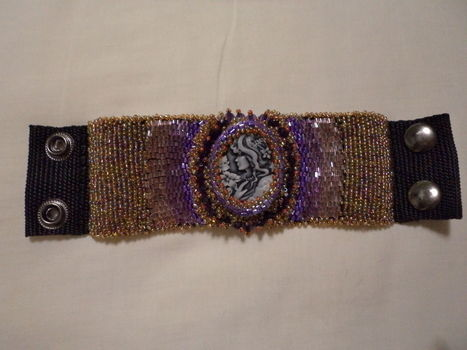 With cameo centerpiece .  Make a beaded cuff by beading and embroidering with thread, beads, and glue. Inspired by clothes & accessories. Creation posted by Anria O. Difficulty: Easy. Cost: Cheap.