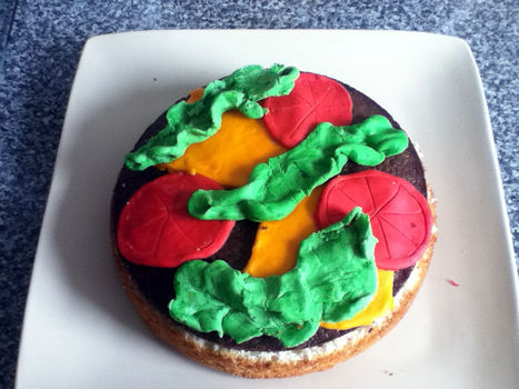 A sponge cake made to look like a burger! .  Decorate a food shaped cake in under 120 minutes by cooking, baking, decorating food, and cake decorating with food coloring, cake, and cake. Inspired by burgers. Creation posted by SAMFOB. Difficulty: Simple. Cost: Absolutley free.