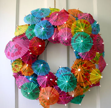Get the party started with this festive wreath made from cocktail umbrellas! .  Free tutorial with pictures on how to make a recycled wreath in 2 steps by decorating and papercrafting with wreath form and cocktail umbrellas. How To posted by Camilla F. Difficulty: Simple. Cost: Cheap.