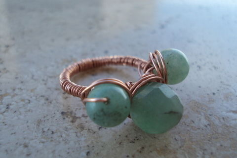 The perfection of three green beads on a copper frame .  Make a wire wrapped ring in under 35 minutes by beading and wireworking with wire cutters, round nose pliers, and copper wire. Creation posted by Juliet J. Difficulty: Simple. Cost: Absolutley free.