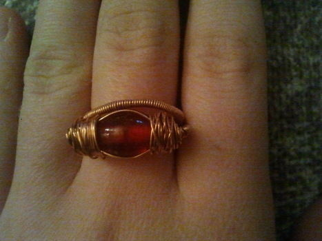 Wire and a red bead ring. .  Make a wire wrapped ring in under 15 minutes by jewelrymaking and wireworking with jewelry wire and copper wire. Inspired by christmas. Creation posted by lolly p. Difficulty: Easy. Cost: Absolutley free.