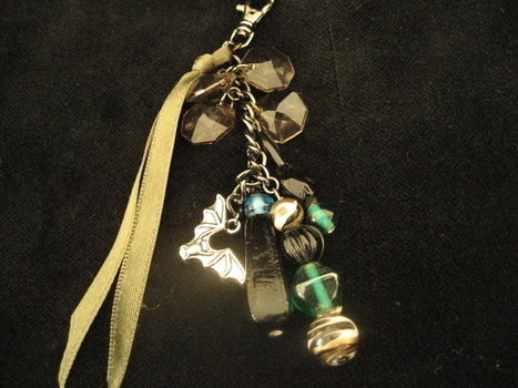 Made this for a recent swap  .  Make a charm keyring in under 30 minutes by beading with ribbon, jump rings, and charms. Inspired by gothic. Creation posted by Arty Kitkat. Difficulty: Easy. Cost: Absolutley free.