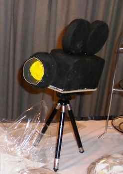 Camera Cake for Hollywood themed Bridal Shower. .  Decorate an object cake in under 90 minutes by baking and decorating food with cardboard, wood, and fondant. Creation posted by Cheryl H.  in the Recipes section Difficulty: 3/5. Cost: Absolutley free.