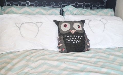Embroidered animal ear pillows give you cute ears at bedtime! .  Free tutorial with pictures on how to make a stitched cushion in 11 steps by embroidering with pillow case, transfer pen, and tracing paper. How To posted by Cat Morley.  in the Needlework section Difficulty: Simple. Cost: Cheap.