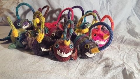 Happy little Angler fish waiting to chomp whoever they can. .  Make a fish plushie in under 120 minutes by knitting and hand sewing with yarn, knitting needles, and safety eyes. Creation posted by Zoe S.  in the Yarncraft section Difficulty: Simple. Cost: 3/5.