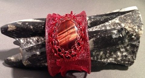 Wire Mesh Bangle with a Viking Knitted Red Tigers Eye Camachon .  Free tutorial with pictures on how to make a bangle in under 60 minutes by jewelrymaking, wireworking, and hand sewing with wire mesh, cabachon, and base. How To posted by SheShellsJewellery.  in the Jewelry section Difficulty: Easy. Cost: 3/5. Steps: 1