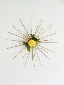 Sunburst wall decor with an added spring twist! .  Free tutorial with pictures on how to make a wall decal in under 120 minutes by decorating with styrofoam ball, dowels, and spray paint. How To posted by Lydia L.  in the Home + DIY section Difficulty: Simple. Cost: Cheap. Steps: 5