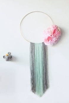 Quick and easy wreath using a bit of yarn and paper flowers. .  Free tutorial with pictures on how to make a floral wreath in under 60 minutes by decorating, knotting, and yarncrafting with macrame hoop, paper peonies, and pipe cleaners. How To posted by Cassandra L.  in the Home + DIY section Difficulty: Easy. Cost: Cheap. Steps: 5
